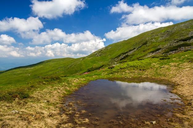 Niebieskie niebo z jaskrawymi białymi chmurami odbijał w małym jeziorze między zielonymi wzgórzami na słonecznym dniu. letnia panorama.
