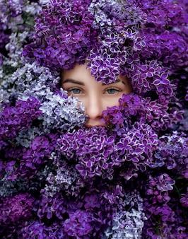 Niebieskie oczy młodej kaukaskiej dziewczyny otoczonej dużą ilością fioletowego bzu, tapeta