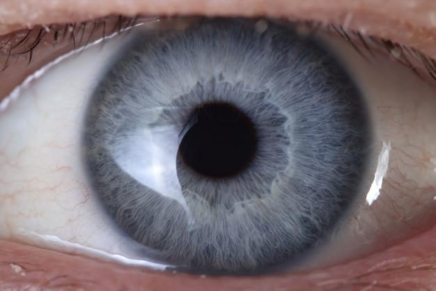 Niebieskie oko z bliska. produkcja kolorowych soczewek kontaktowych
