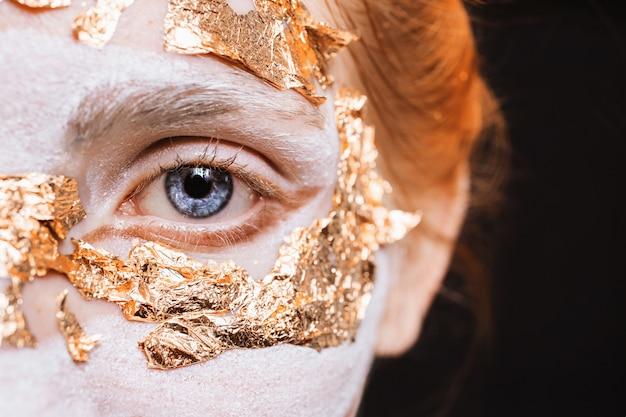 Niebieskie oko zbliżenie. dziewczyna z niezwykłym makijażem ze złotym liściem. anonim. maskarada halloween