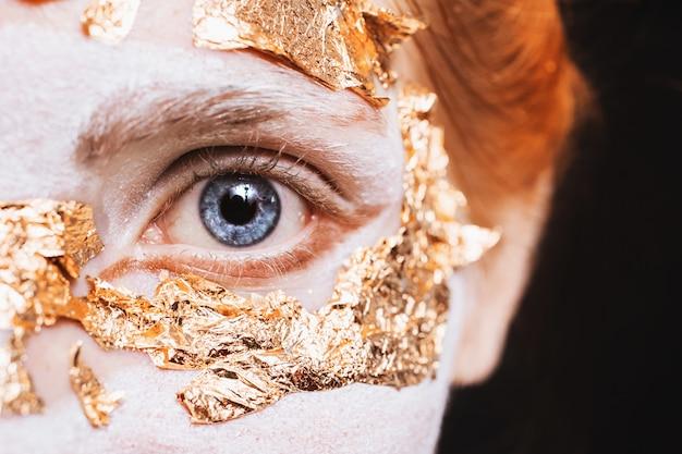 Niebieskie oko zbliżenie. dziewczyna z niezwykłym makijażem ze złotym liściem. karnawał maskujący