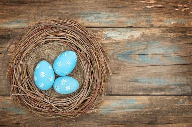 Niebieskie pisanki w ptasie gniazdo na podłoże drewniane - widok z góry