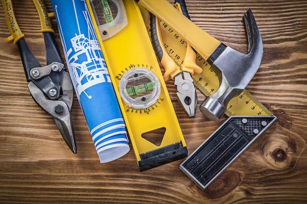 Niebieskie plany, poziom konstrukcji, wypróbuj kwadrat, pazur, młotek, szczypce i stalowy nóż na drewnianej desce