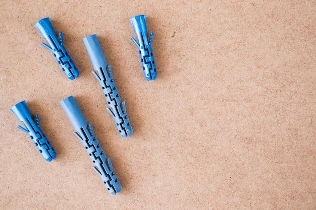 Niebieskie plastikowe kołki ścienne na brązowym tle, wysoki kąt widzenia