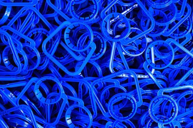 Niebieskie plastikowe uchwyty do łatwego przenoszenia plastikowych pojemników na płyn