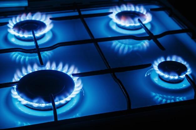 Niebieskie płomienie gazu płonące z kuchennej kuchenki gazowej