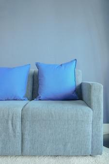 Niebieskie poduszki kolor ustawienie na jasnoniebieskiej kanapie z niebieską ścianą