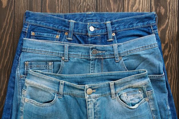 Niebieskie przetarte dżinsy ze szwami, klamrami, guzikami i nitami, tekstura, zbliżenie