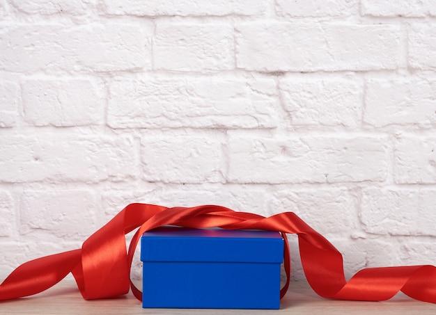 Niebieskie pudełko kartonowe z prezentem i czerwoną wstążką jedwabną na tle ściany z cegły białej