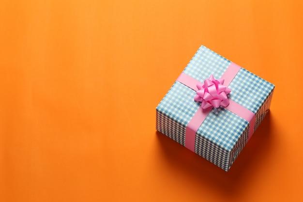 Niebieskie pudełko na boże narodzenie umieszczone na pomarańczowej podłodze z papieru artystycznego i miejsce na kopię.