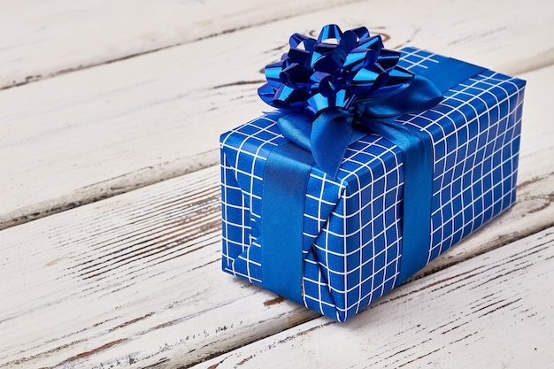 Niebieskie pudełko na drewno. kokarda na prezentowym opakowaniu. sztuka pakowania prezentów.