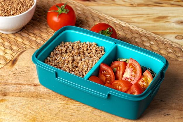 Niebieskie pudełko na lunch z kaszą gryczaną i pomidorami