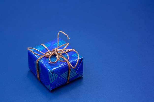 Niebieskie pudełko przewiązane pomarańczową liną na niebieskim tle. skopiuj miejsce.