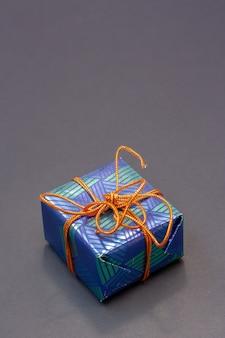 Niebieskie pudełko przewiązane pomarańczową liną na szarym tle. rama pionowa. skopiuj miejsce na górze.