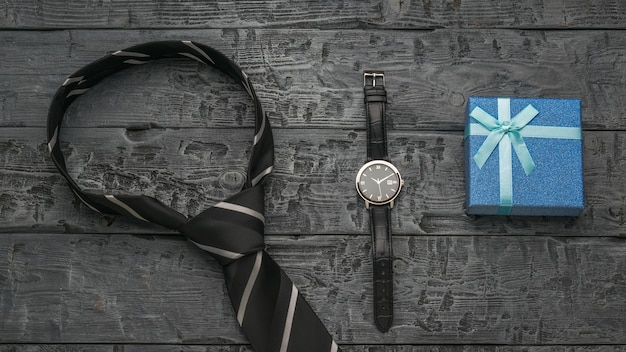 Niebieskie pudełko upominkowe, krawat i zegarek na drewnianym tle.