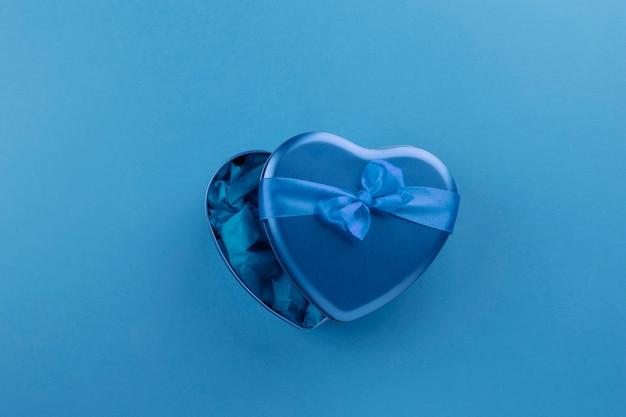 Niebieskie pudełko w kształcie serca ze wstążką na niebieskim tle