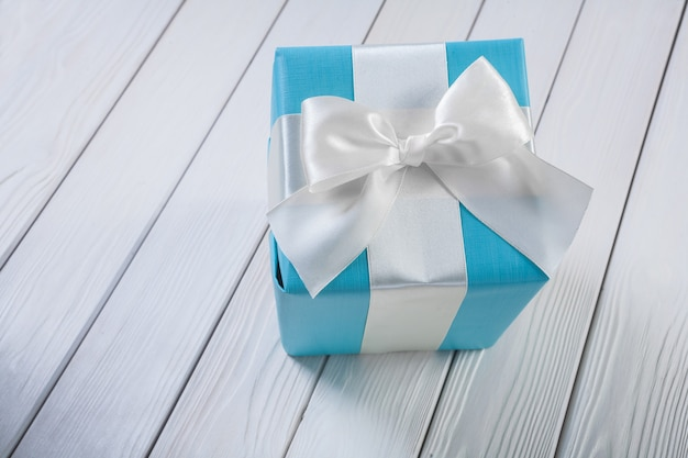 Niebieskie pudełko z białą kokardą na białych drewnianych deskach