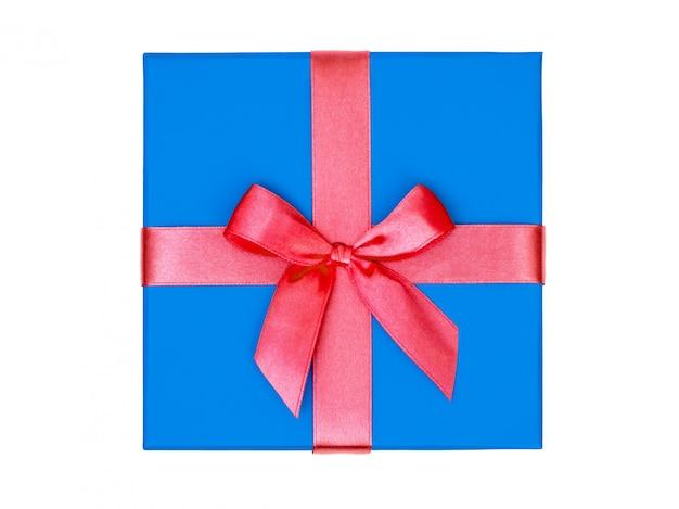 Niebieskie pudełko z czerwoną wstążką na białym tle