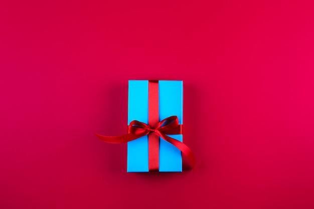 Niebieskie pudełko z czerwoną wstążką na czerwonym tle papieru. walentynki, urodziny, koncepcja wakacje. widok z góry, leżał płasko, miejsce