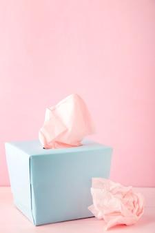 Niebieskie pudełko z papierowymi chusteczkami i zużyte zmięte serwetki
