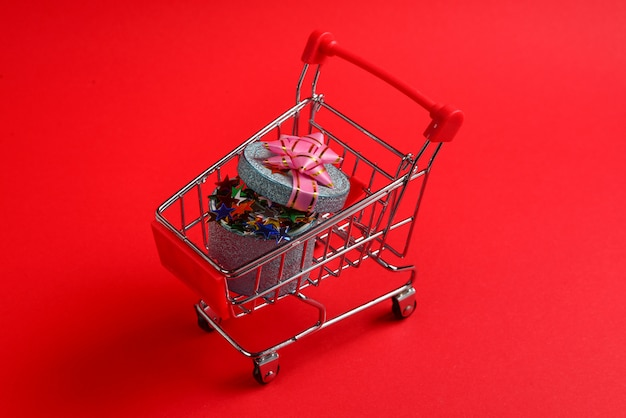 Niebieskie pudełko z różową kokardą w koszyku na czerwonym tle.