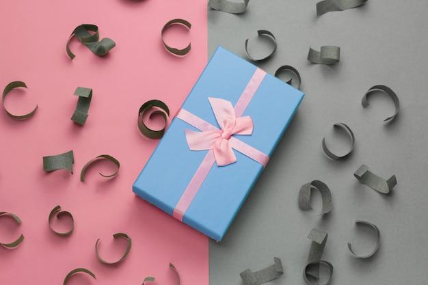 Niebieskie pudełko z świąteczną różową kokardką w widoku z góry na szarym i pastelowym różowym tle z papierowymi konfetti
