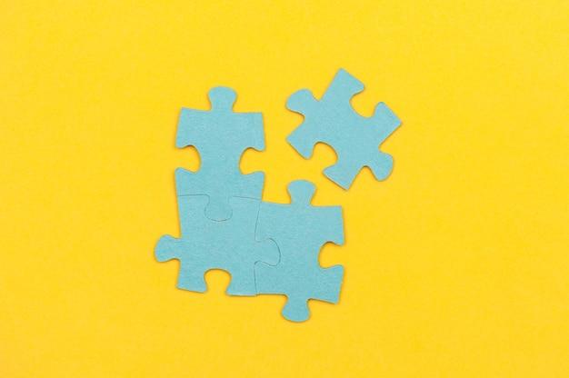 Niebieskie puzzle z brakującym elementem na żółtym tle