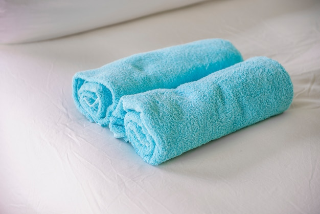 Niebieskie ręczniki na białym łóżku