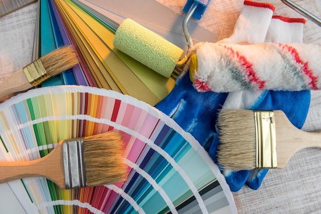 Niebieskie rękawice ochronne z paletą kolorów i pędzlami do naprawy domu lub renowacji na desce. zestaw wyposażenia