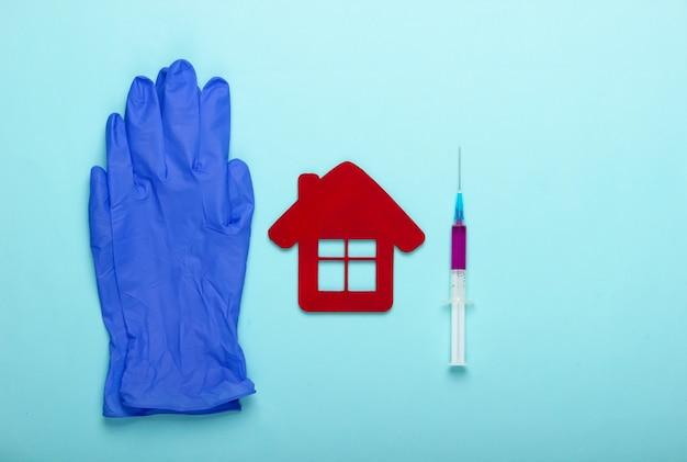 Niebieskie rękawiczki lateksowe, figurka budynku szpitala i strzykawka na niebieskim tle. szczepionka. widok z góry