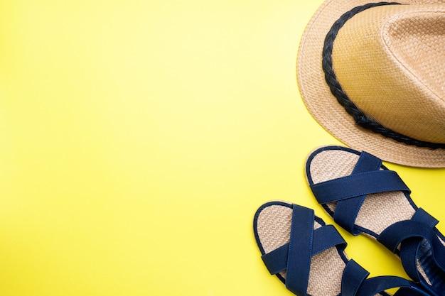 Niebieskie sandały i kapelusz na żółtym tle z miejsca na kopię. koncepcja letnie wakacje. leżał płasko