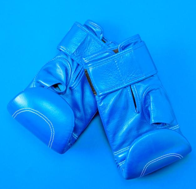 Niebieskie skórzane rękawice bokserskie sportowe na czerwonym tle