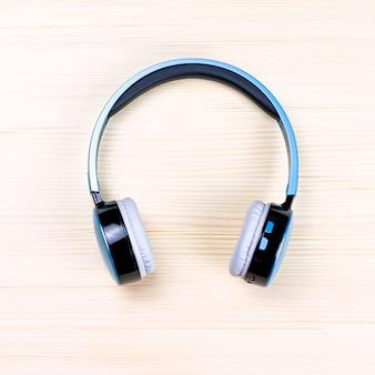 Niebieskie słuchawki bezprzewodowe z bliska na drewnie