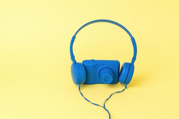 Niebieskie słuchawki i niebieski aparat na żółtym tle. stylowy sprzęt do robienia zdjęć i nagrywania filmów.