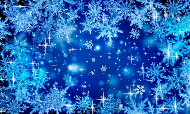 Niebieskie śnieżne świąteczne tło z lodowymi płatkami śniegu i blaskiem gwiazd