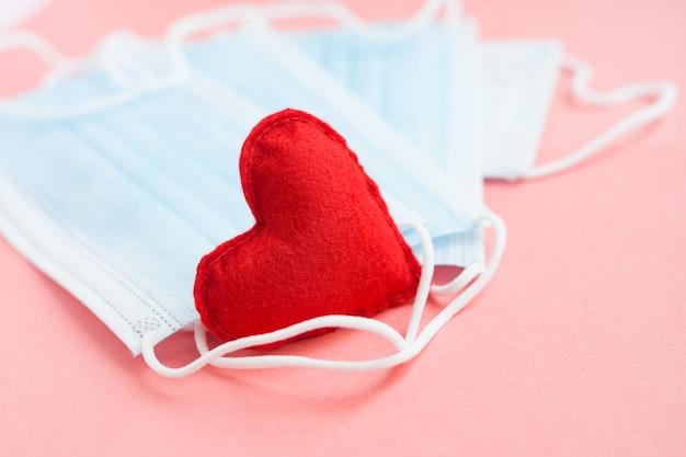 Niebieskie sukienne medyczne maski z czerwonym sercem na różowym tle. odważne serce i wdzięczność dla wszystkich pracowników medycyny. koronawirus, covid-19, pandemia podczas kwarantanny.