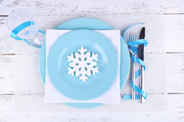 Niebieskie talerze, nóż, widelec, serwetka i świąteczne dekoracje na drewnianym tle