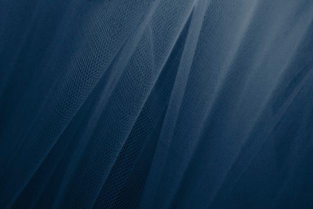 Niebieskie tiulowe draperie teksturowane w tle