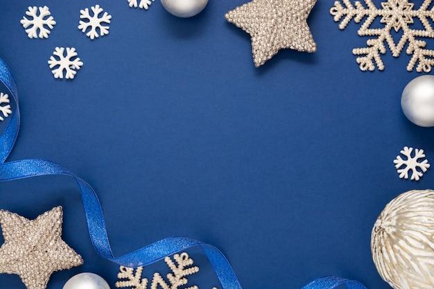 Niebieskie tło boże narodzenie minimalistycznym stylu ze srebrnymi płatkami śniegu, bombkami i niebieską wstążką. niebieski makiety z miejscem na tekst.
