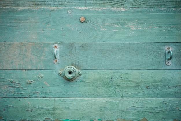 Niebieskie tło desek, drewniane teksturowane stare tło z gwoździami, żelazko i armatura, metalowy zamek