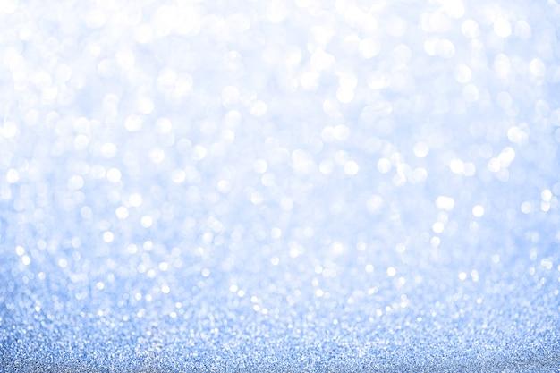 Niebieskie tło niewyraźne brokat. błyszcząca i błyszcząca tekstura na boże narodzenie i nowy rok lub sezonową dekorację tapet