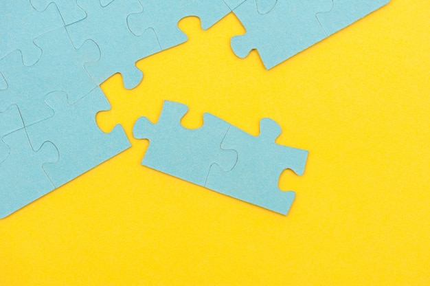 Niebieskie tło puzzli z brakującym elementem na żółtym tle widok z góry