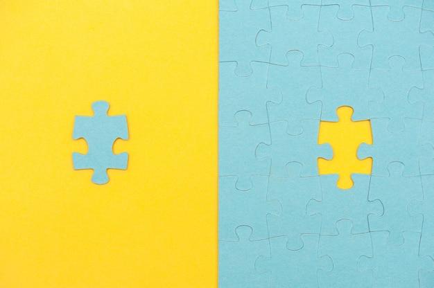 Niebieskie tło układanki z brakującym elementem na żółtym tle widok z góry