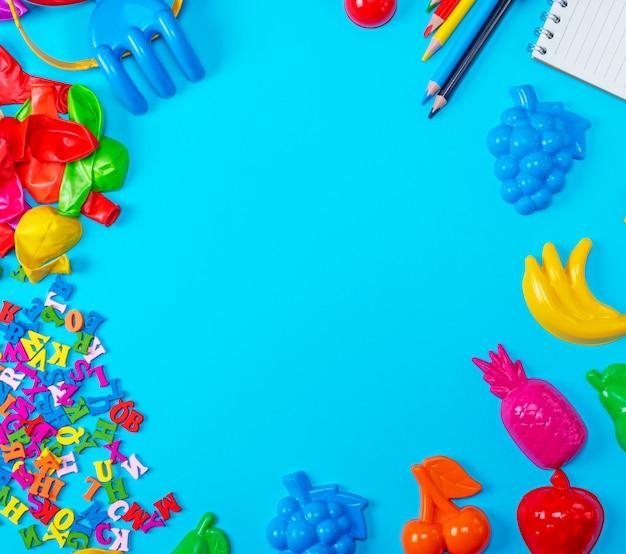 Niebieskie tło z plastikowymi zabawkami dla dzieci, ołówki, balony i drewniane litery
