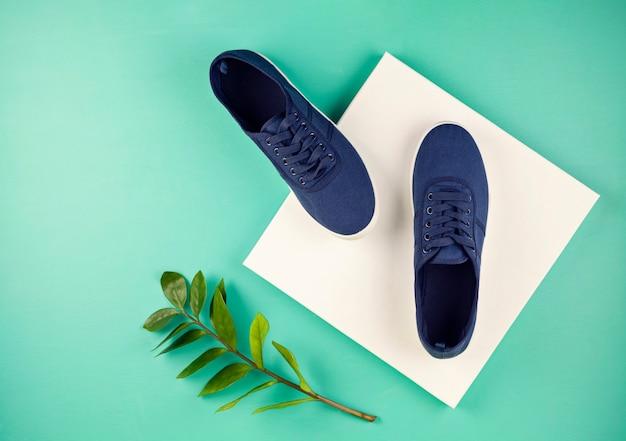 Niebieskie trampki morskie buty na seledynowym backgroung