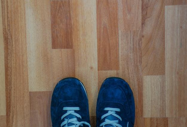 Niebieskie trampki na drewnianej podłodze