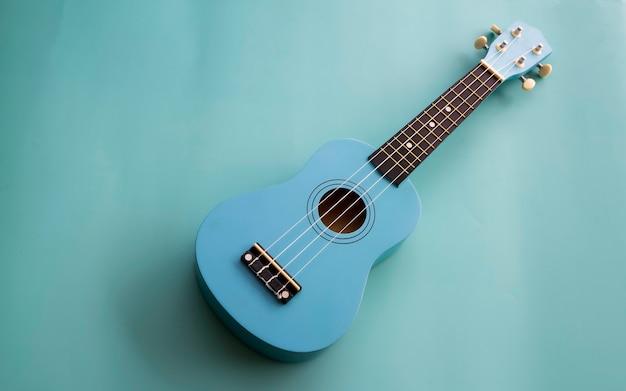 Niebieskie ukulele na pastelowym tle. instrument akustyczny