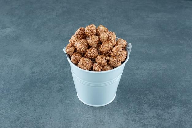 Niebieskie wiadro cukierków popcornu na marmurowym tle. zdjęcie wysokiej jakości