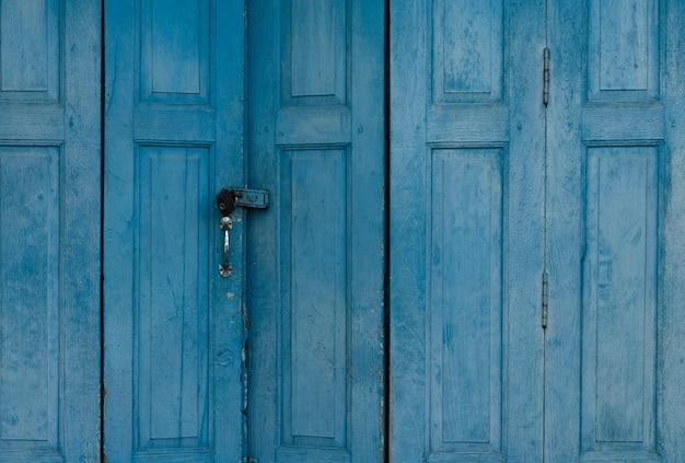 Niebieskie zamknięte drzwi drewniane. rocznika dzwi wejściowy abstrakta tło. opuszczony stary dom. stare drewniane drzwi tekstury. zamknij drzwi starego domu.