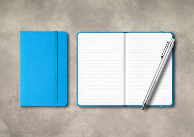 Niebieskie, zamknięte i otwarte zeszyty w linie z długopisem. makieta na białym tle na betonowym tle